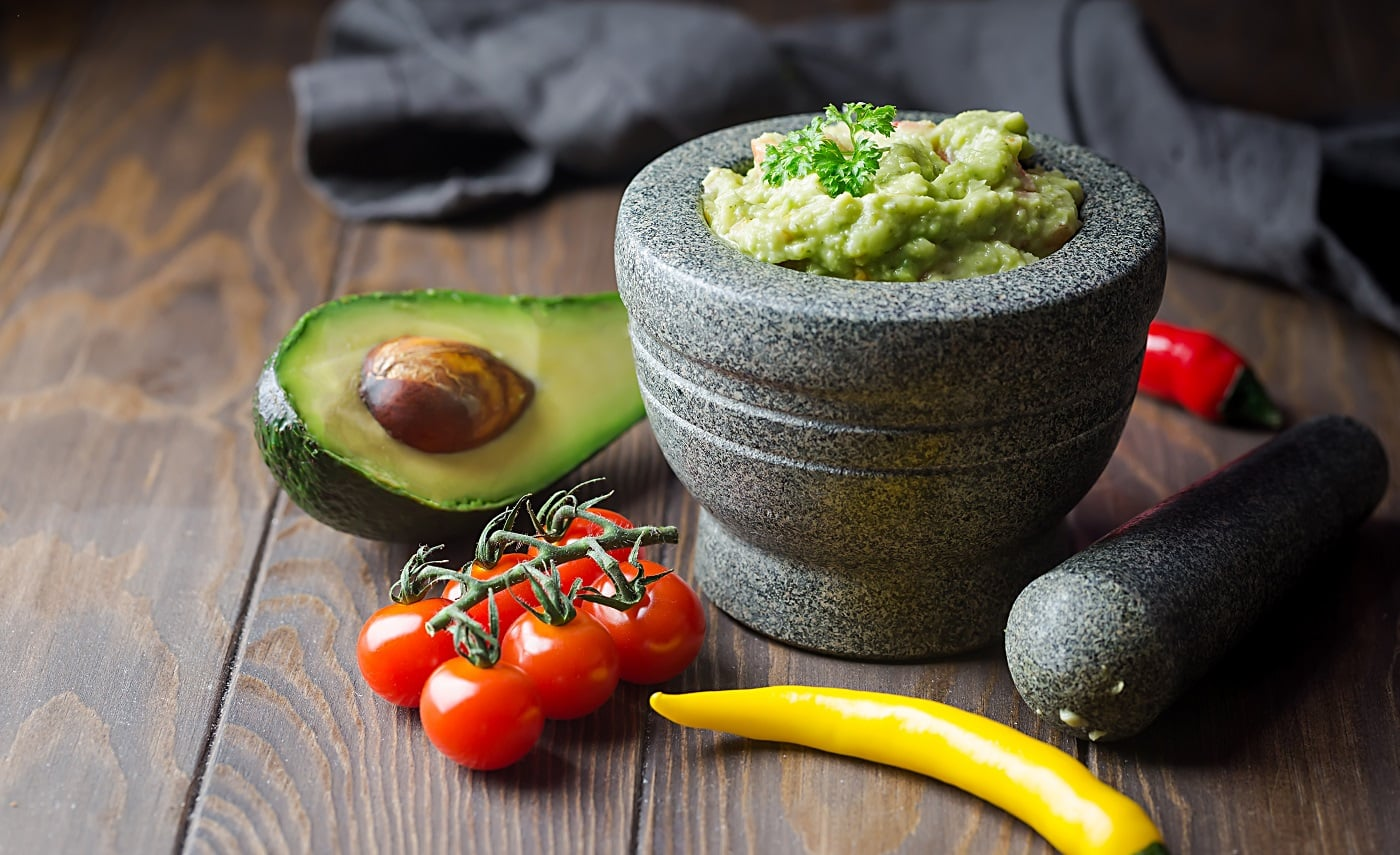 Traditional Mexican Guacamole sauce with avocado in a mortar or molcajete over dark wooden background