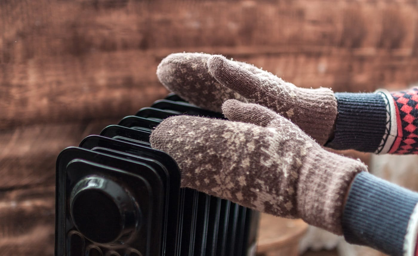 Women's hands in Christmas, warm, winter mittens on the heater. Keep warm in the winter, cold evenings. Heating season