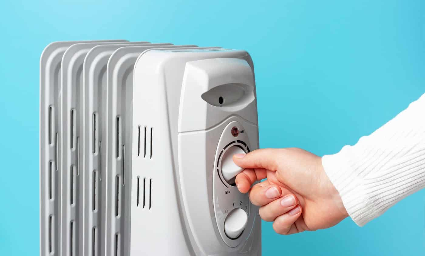 The girl turns on the heater on the blue background, side view