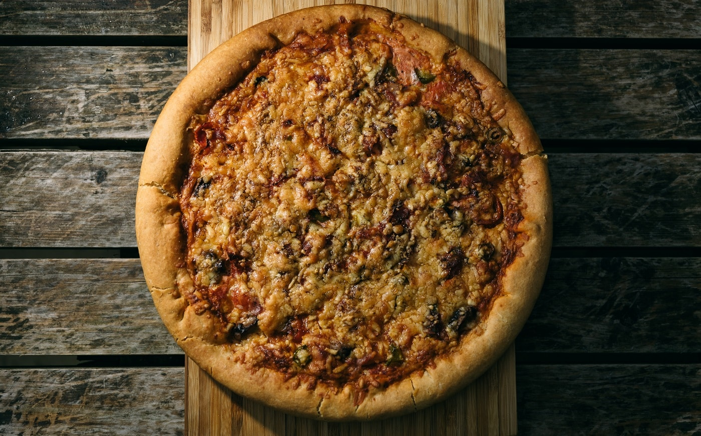 A high angle shot of a freshly baked pizza on a wooden surface