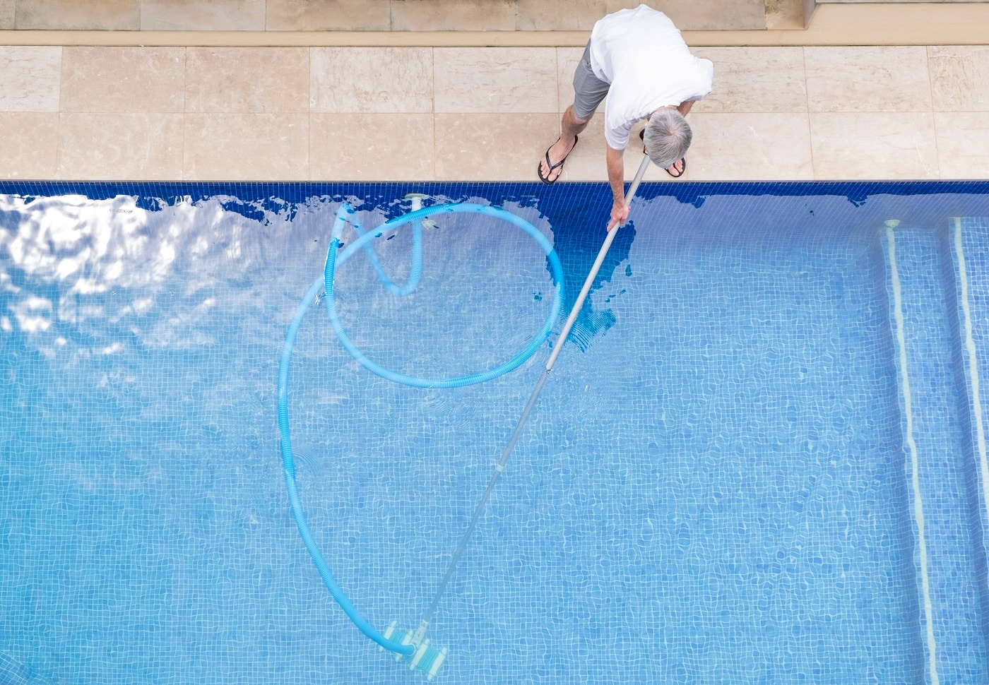 top view of man cleaning a swimming pool