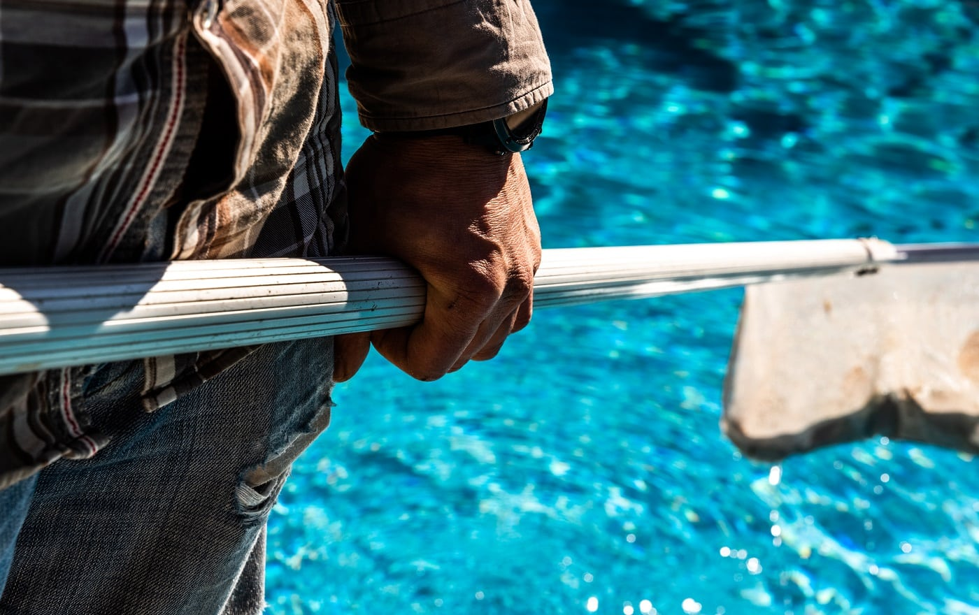 Maintenance man using a pool net leaf skimmer rake in summer to leave ready for bathing his pool.