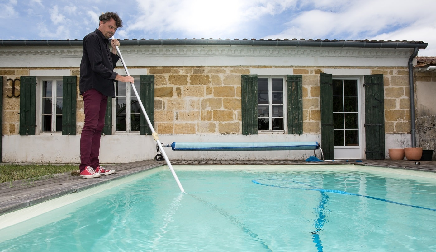 Man cleaning blue swimming pool with vacuum cleaner