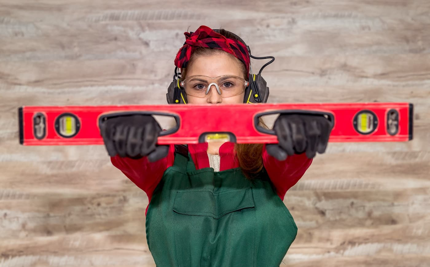 Selective focus on woman eyes with spirit level in carpentry