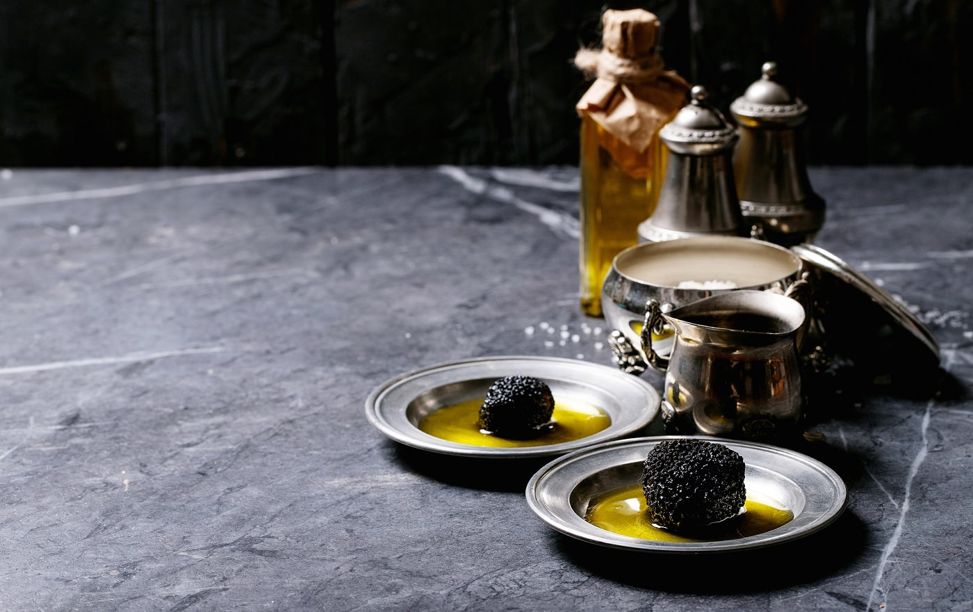Truffle mushroom served with truffle infused olive oil and sea salt with truffles over a black texture background