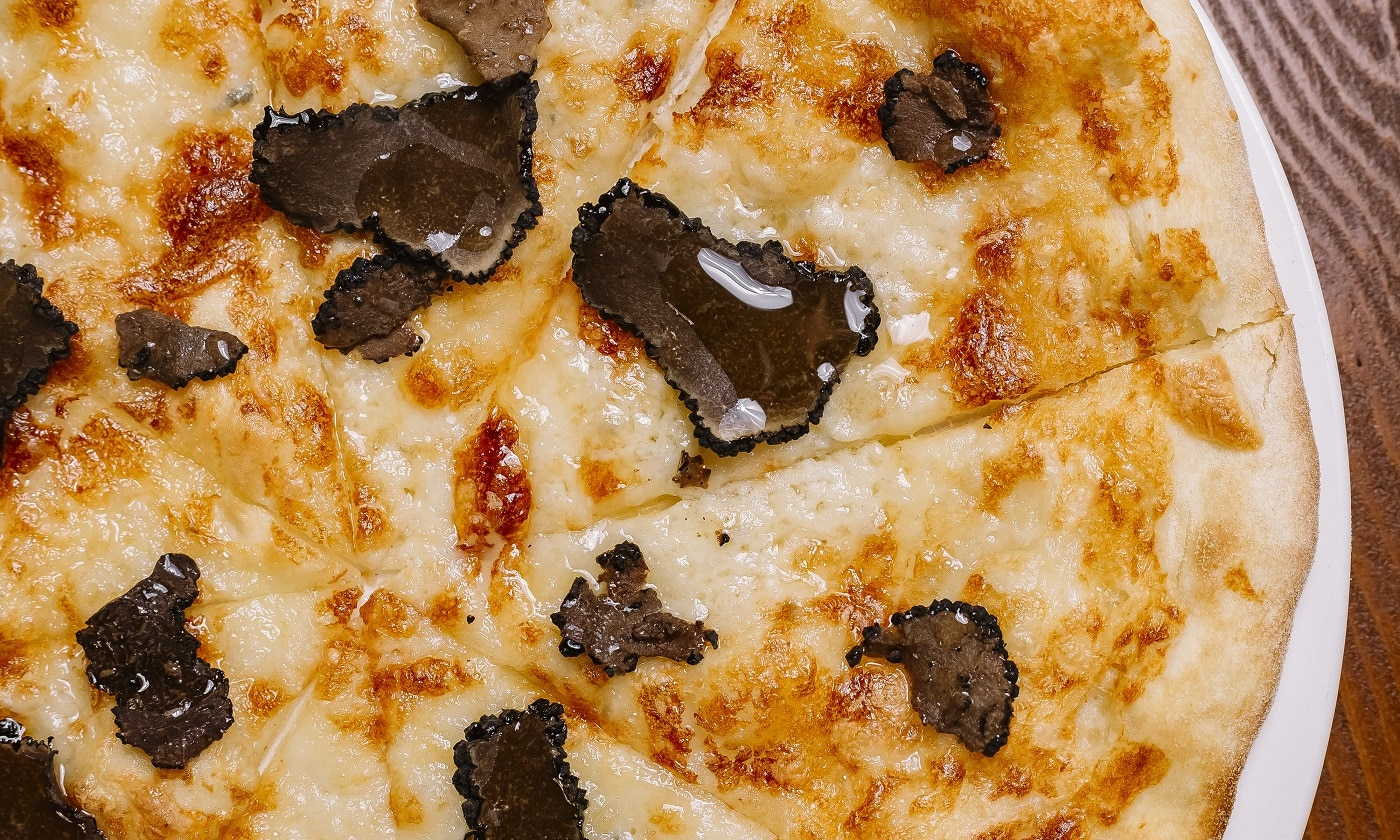 close up of truffle pizza garnished with olive oil