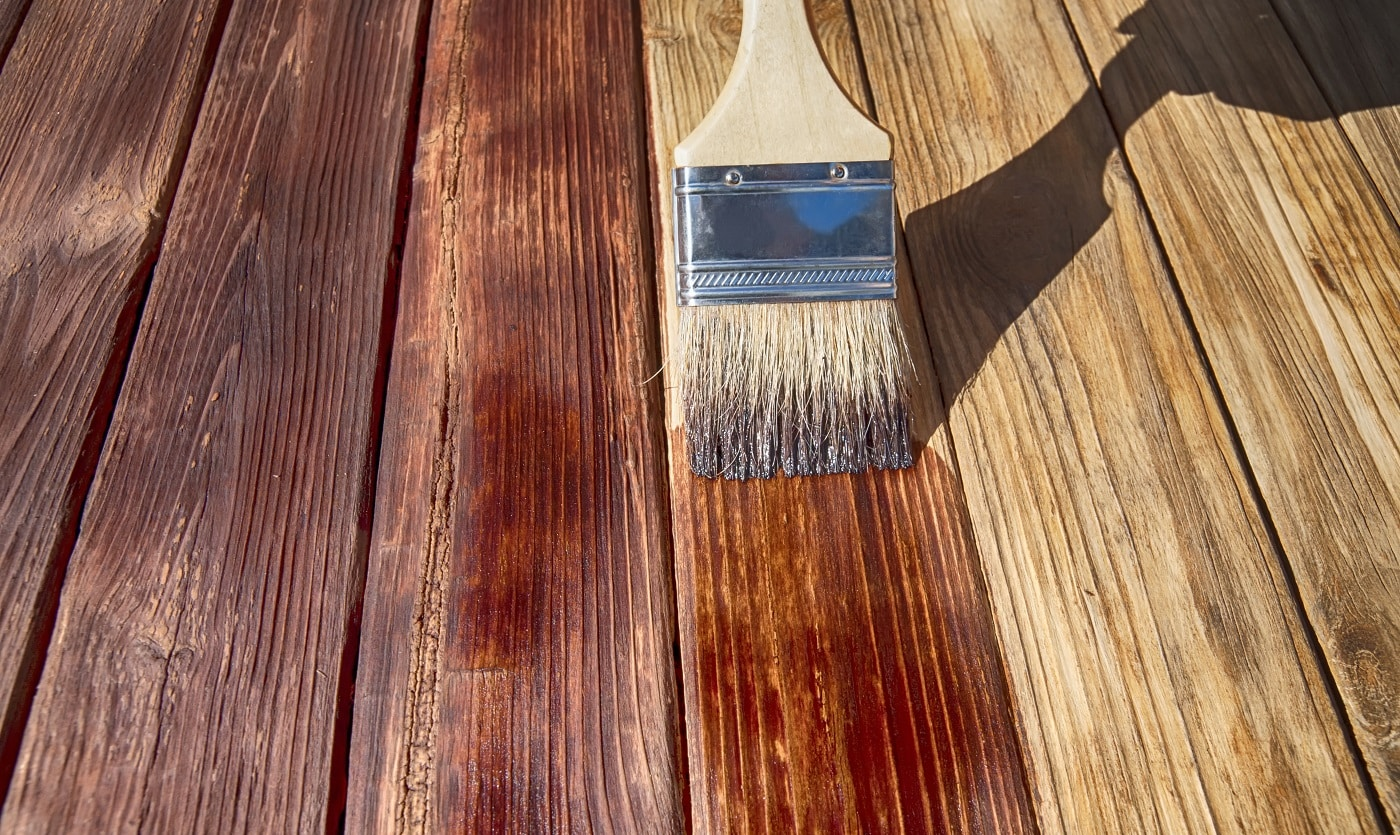 a wooden brush covers the wooden plank surface with a dark red stain front side view close up