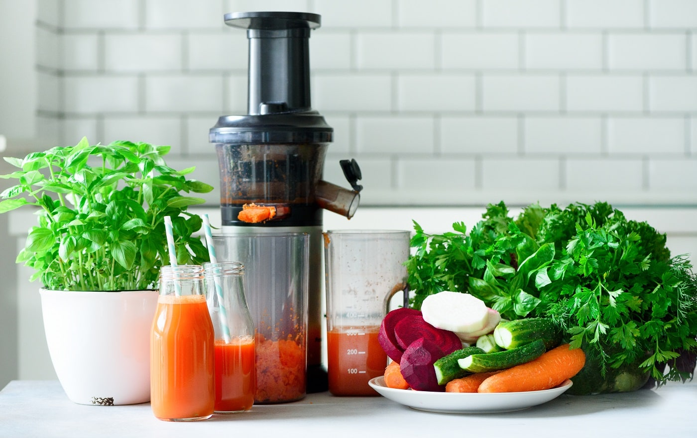 Woman making fresh drink. Juicer and carrot juice. Fruits in background. Clean eating, detox concept