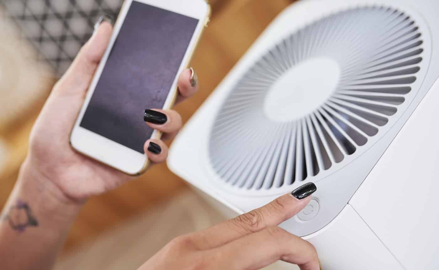 Close-up image of woman turning on air conditioner and using smart home application on her phone to manage temperature