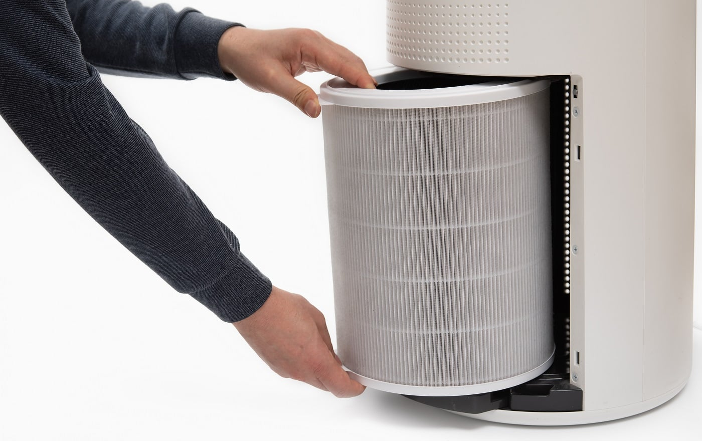A man's hand turning an air purifier's filter into a new one