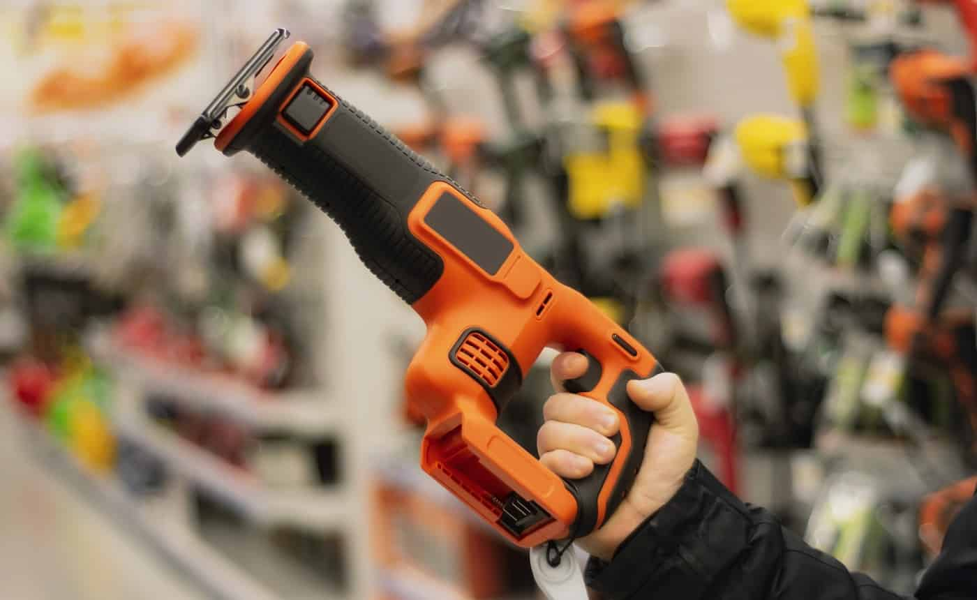Man holds an orange reciprocating saw for repair work against the backdrop of showcases in a hardware store
