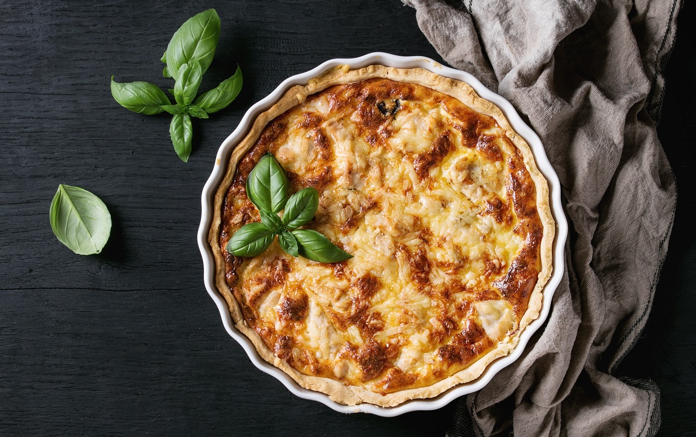 Baked homemade quiche pie in white ceramic form served with fresh greens and textile towel on black wooden burned background. Flat lay with copy space