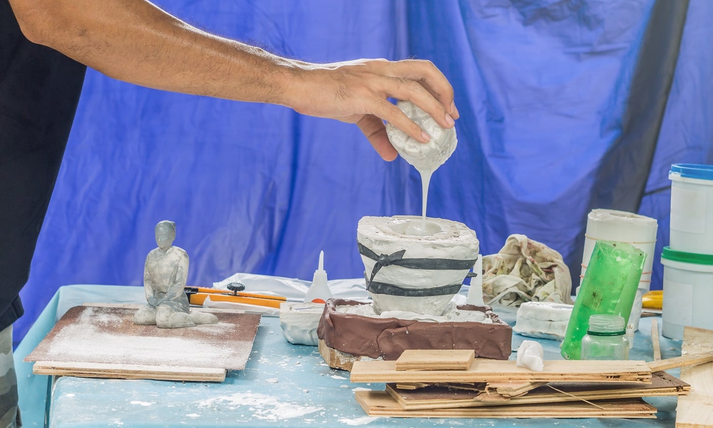 Artist pouring liquid resin in a mold to make a female figure