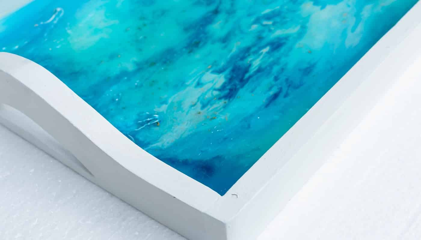 A closeup shot of a white tray with epoxy resin art with blue alcohol inks