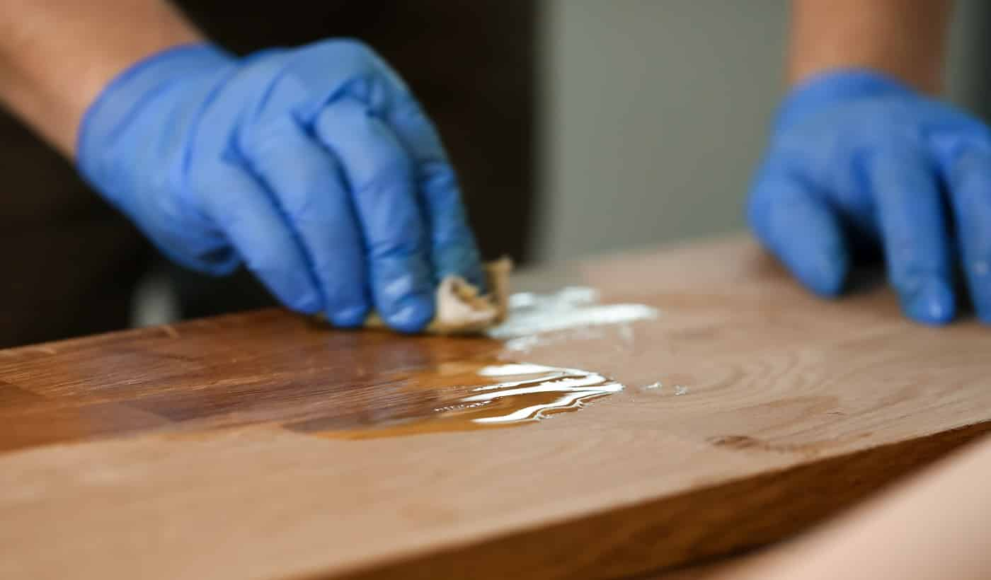 Close-up of woodworker hands in protective gloves covering wooden surface. Joiner lacquering part of furniture. Carpentry work and joinery processing concept