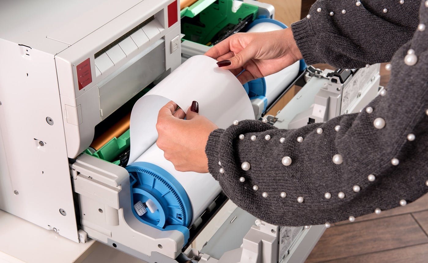 Woman adjusting a roll of new photo paper on a photographic printer in a printing house or studio in a close up view of her hands
