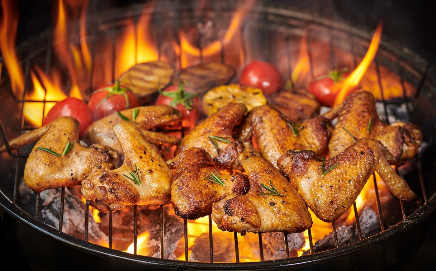 Grilled chicken wings on the flaming grill with Grilled vegetables in barbecue sauce with pepper seeds rosemary, salt. top view with copy space. tasty snack. Flat lay. Healthy lunch menu. Diet food.