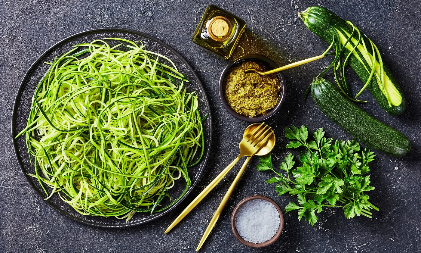Zucchini pasta, zoodles on a black plate on a grey concrete table with basil sauce pesto, golden fork, spoon and ingredients, horizontal view from above, flat lay,