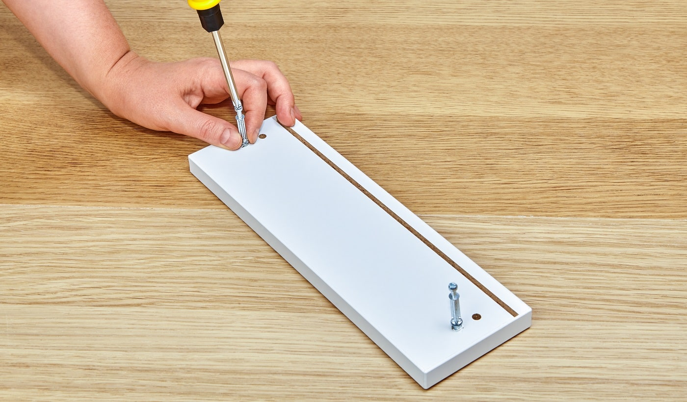 The furniture assembler tightens the connector bolts into a piece of wooden furniture with a screwdriver, with one hand he holds the furniture, the other tightens the bolt, flat pack furniture assembly.