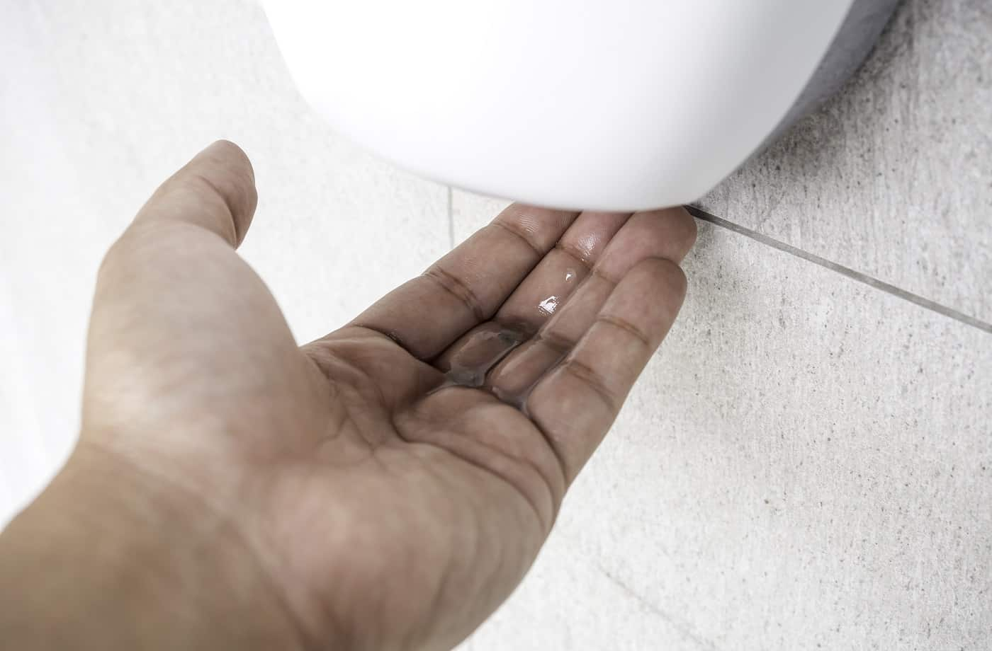Close-up alcohol gel in hand from white automatic sanitizer hand gel on the wall. Cleaning hand with antibacterial hand disinfectant from sanitizer dispenser.