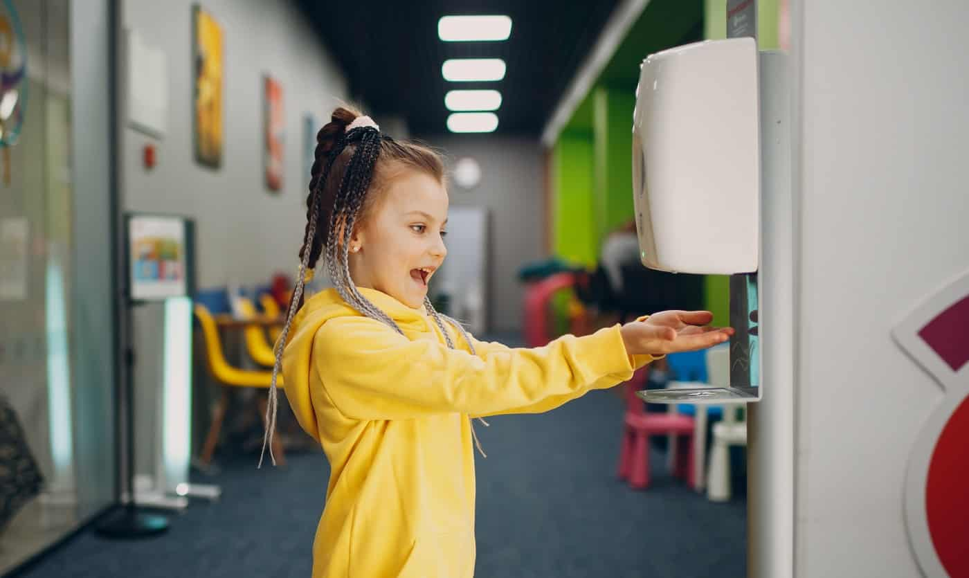 Child girl using automatic alcohol gel dispenser spraying on hands sanitizer machine antiseptic disinfectant, new normal life after Coronavirus COVID-19 pandemia.