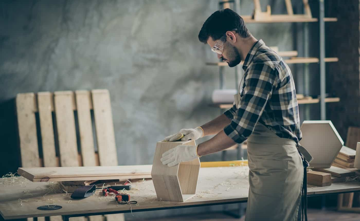 Profile side photo of focused man worker work with wooden shelf restore renew furniture polish surface in home garage