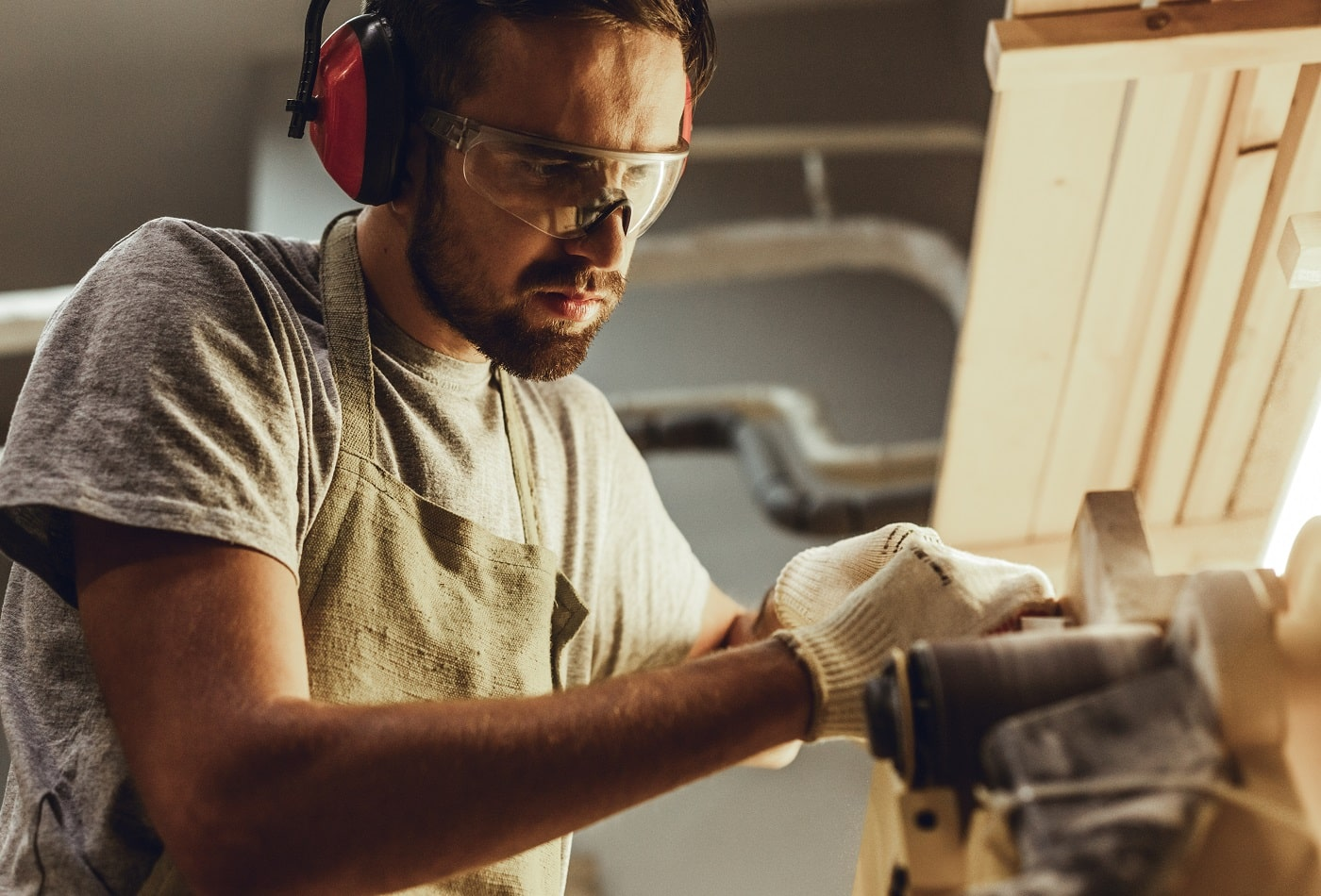 Handsome bearded guy in protection goggles and earmuffs making small timber part on belt sander in workshop