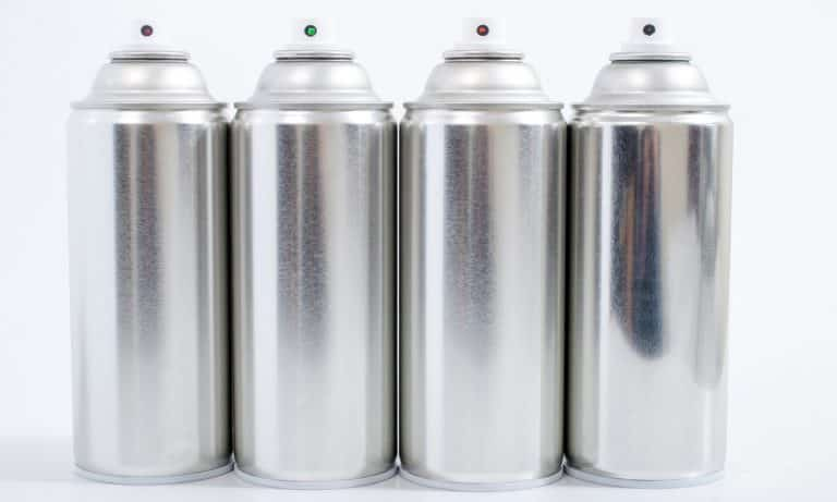 Close up view of silver spray cans on a white background.