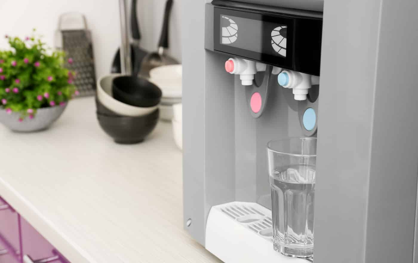 Modern water cooler with glass on kitchen table