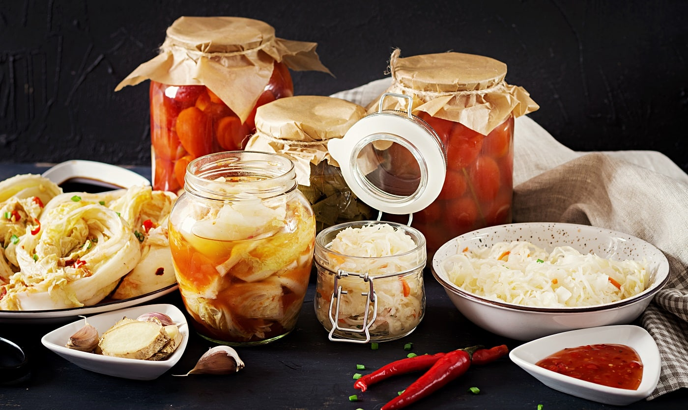 Fermented food. Vegetarian food concept. Cabbage kimchi, tomatoes marinated, sauerkraut sour glass jars over rustic kitchen table. Canned food concept. Copy space