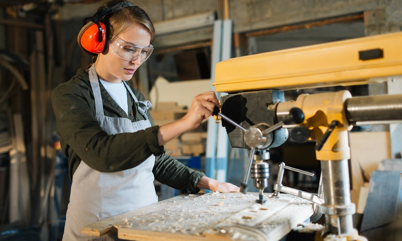 Pretty young carpenter wearing ear and eye protectors while using drill press to make holes in wooden work piece, waist-up portrait