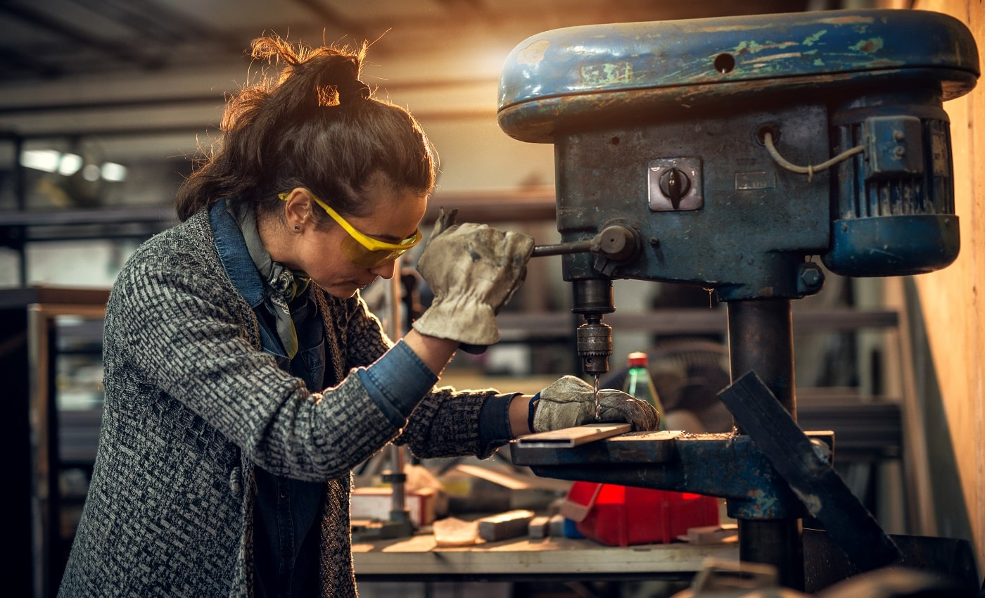 Portrait view of focused serious middle aged professional female carpentry working with an electric drill in the workshop.