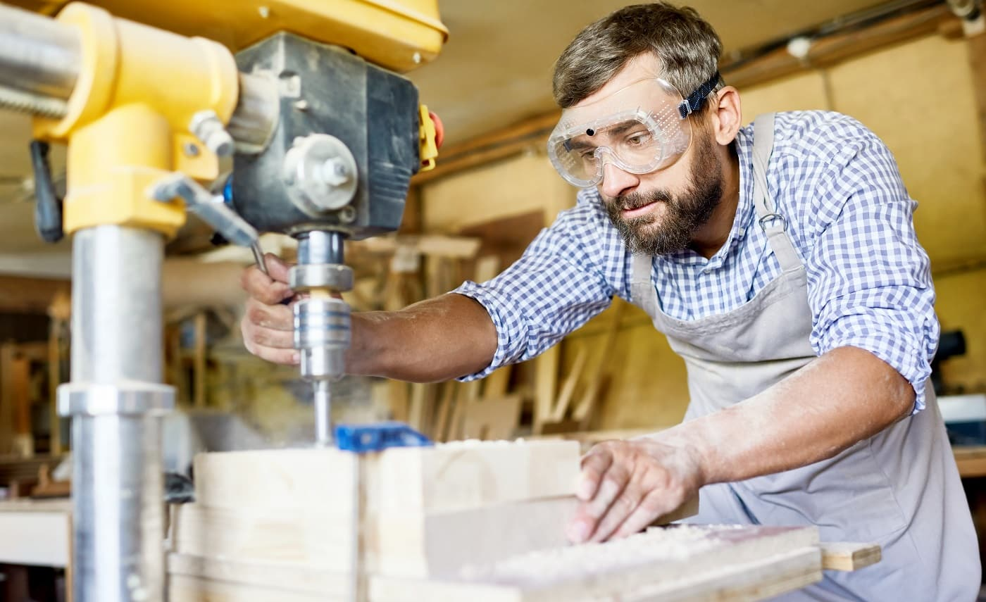 Handsome bearded carpenter wearing safety goggles and apron using drill press machine in order to make holes in wooden plank, interior of spacious workshop on background