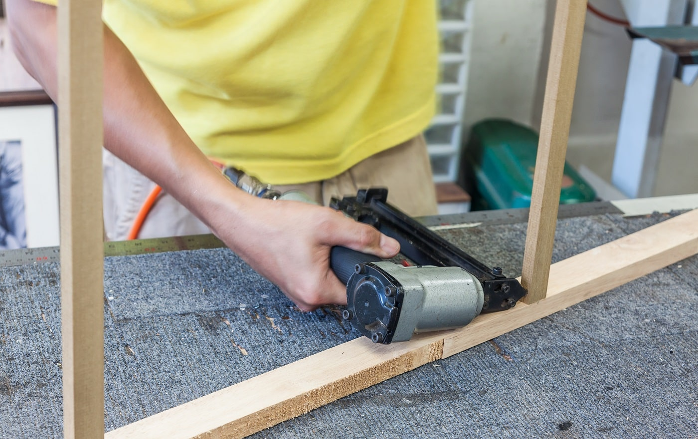 Worker using air nailer shooting nail into log for strengthen holding of wooden frame