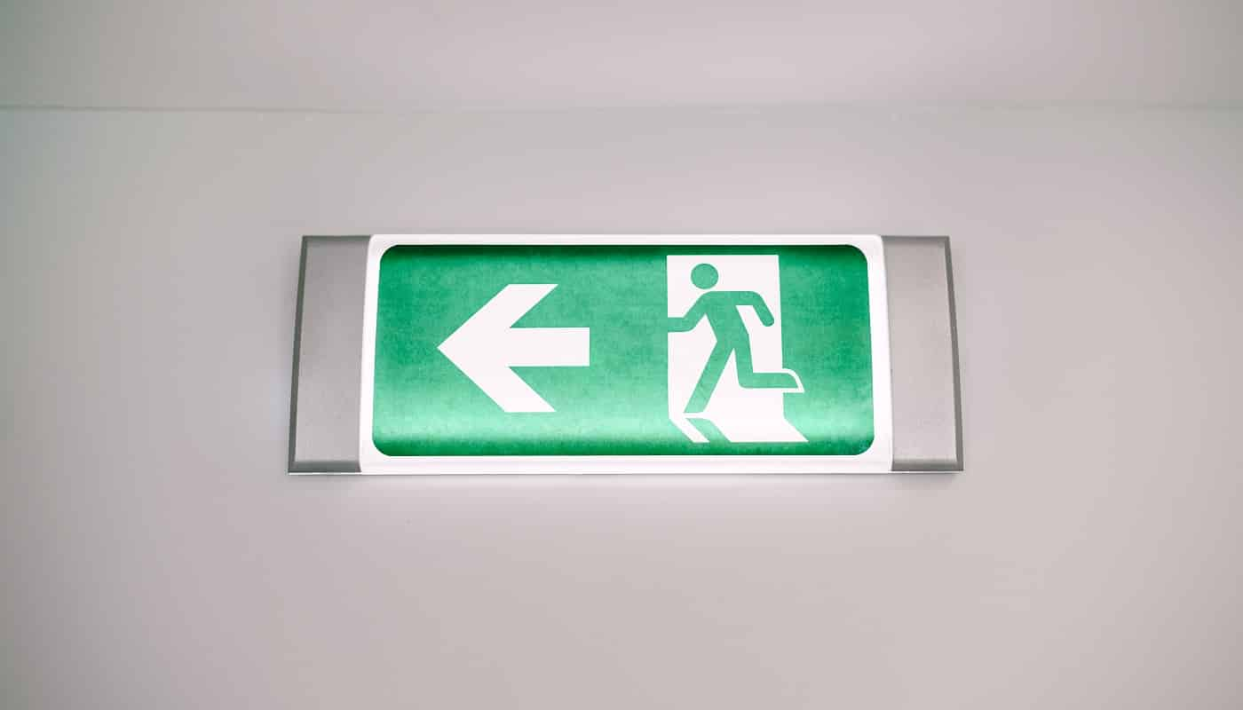 Close-up of a fire safety evacuation light sign with a running man and an arrow on the wall under the ceiling. Green exit indicator. High quality photo