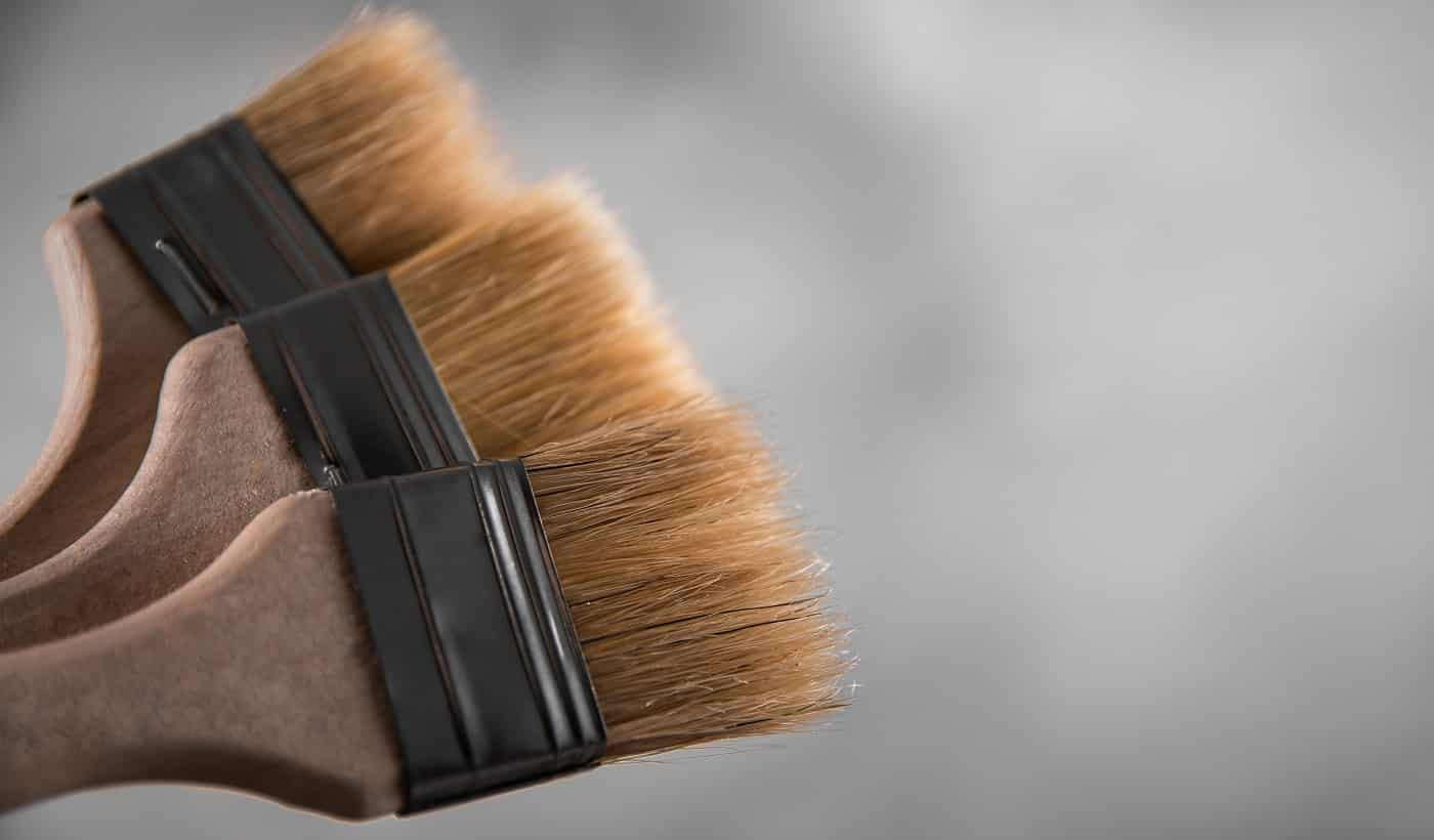 Clean fresh new paint brushes for painting on gray blurred concrete background. Close up with copy empty space for text. Banner for advertising