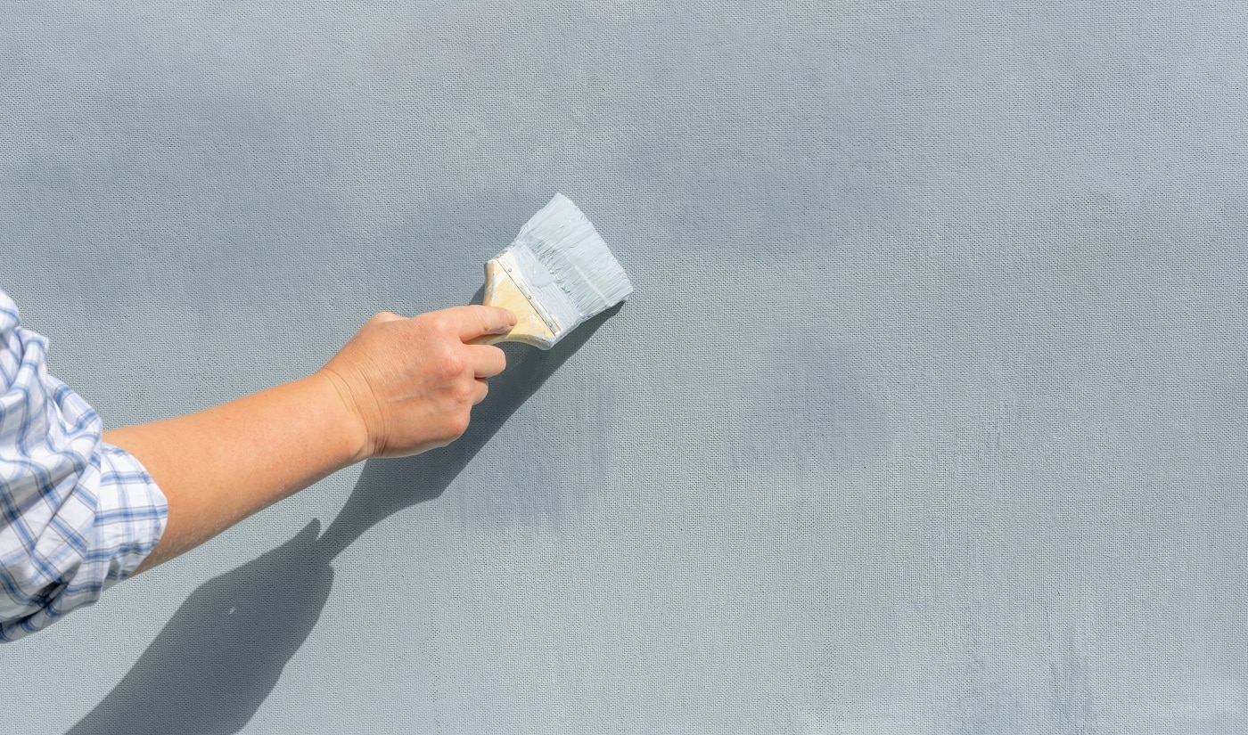 The hand of a repairman with a paintbrush paints the wall blue.