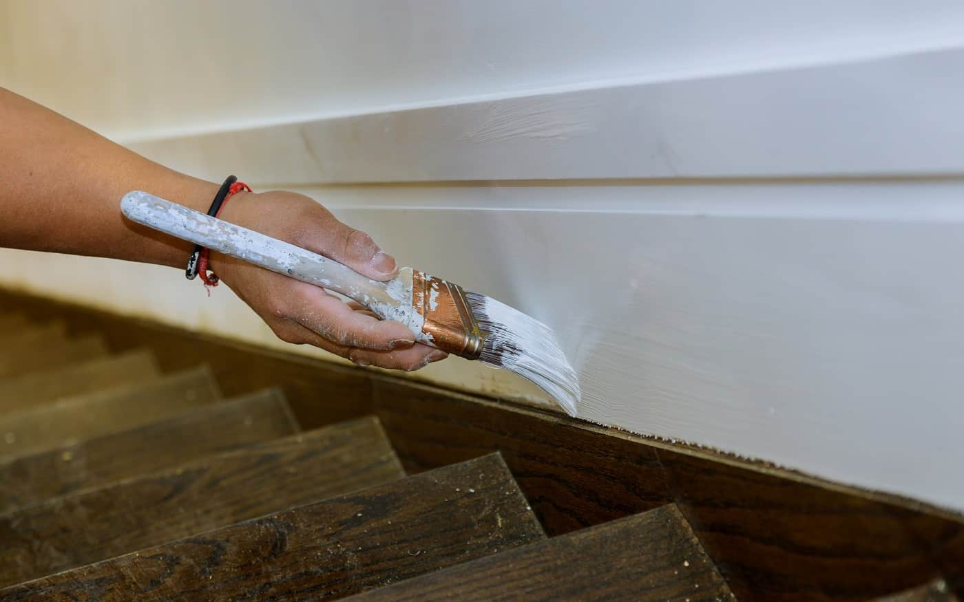Working contractor painter hands with painting the wood molding trim on stairs with brush