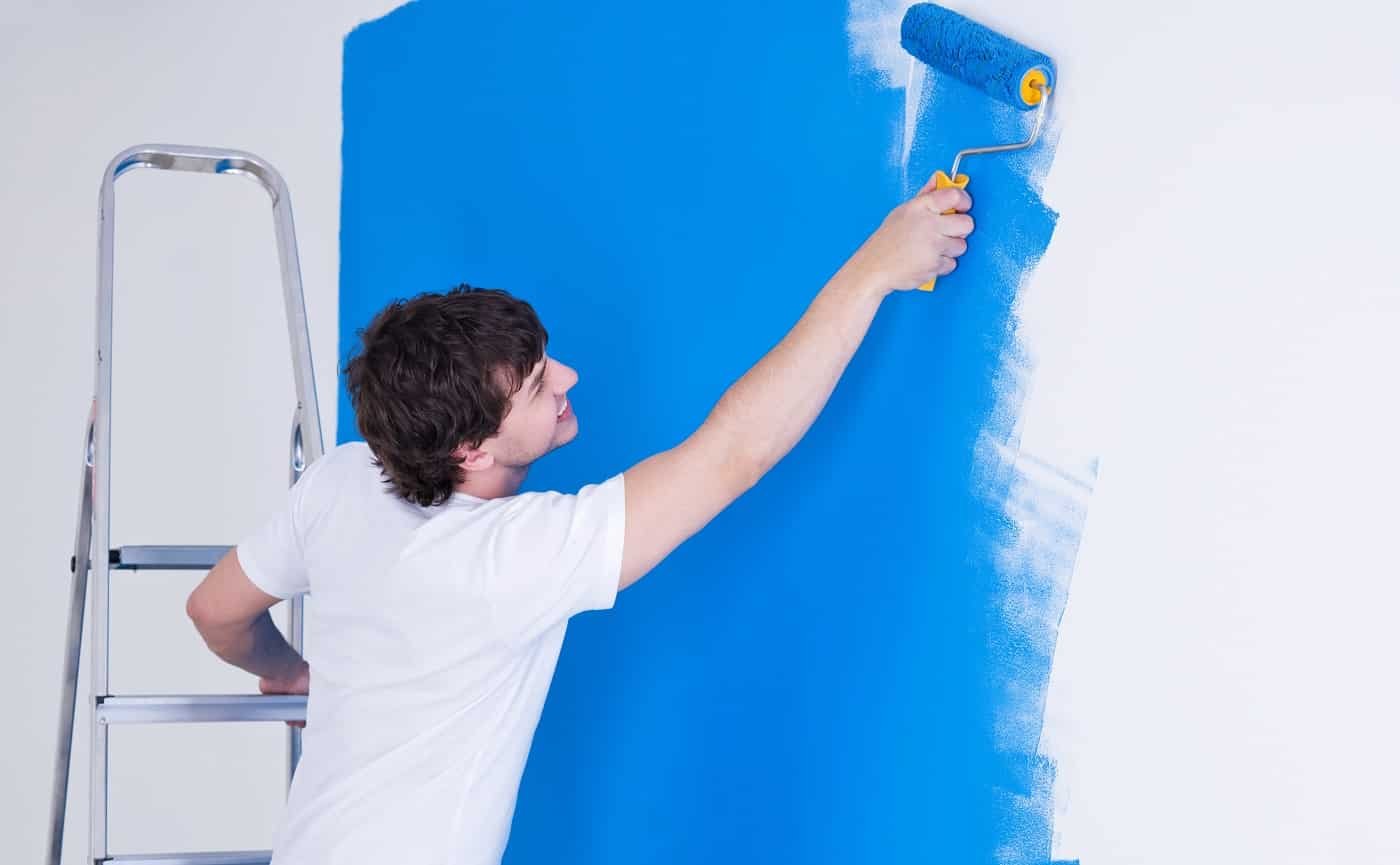 Handsome young man painting the wall in blue - horizontal
