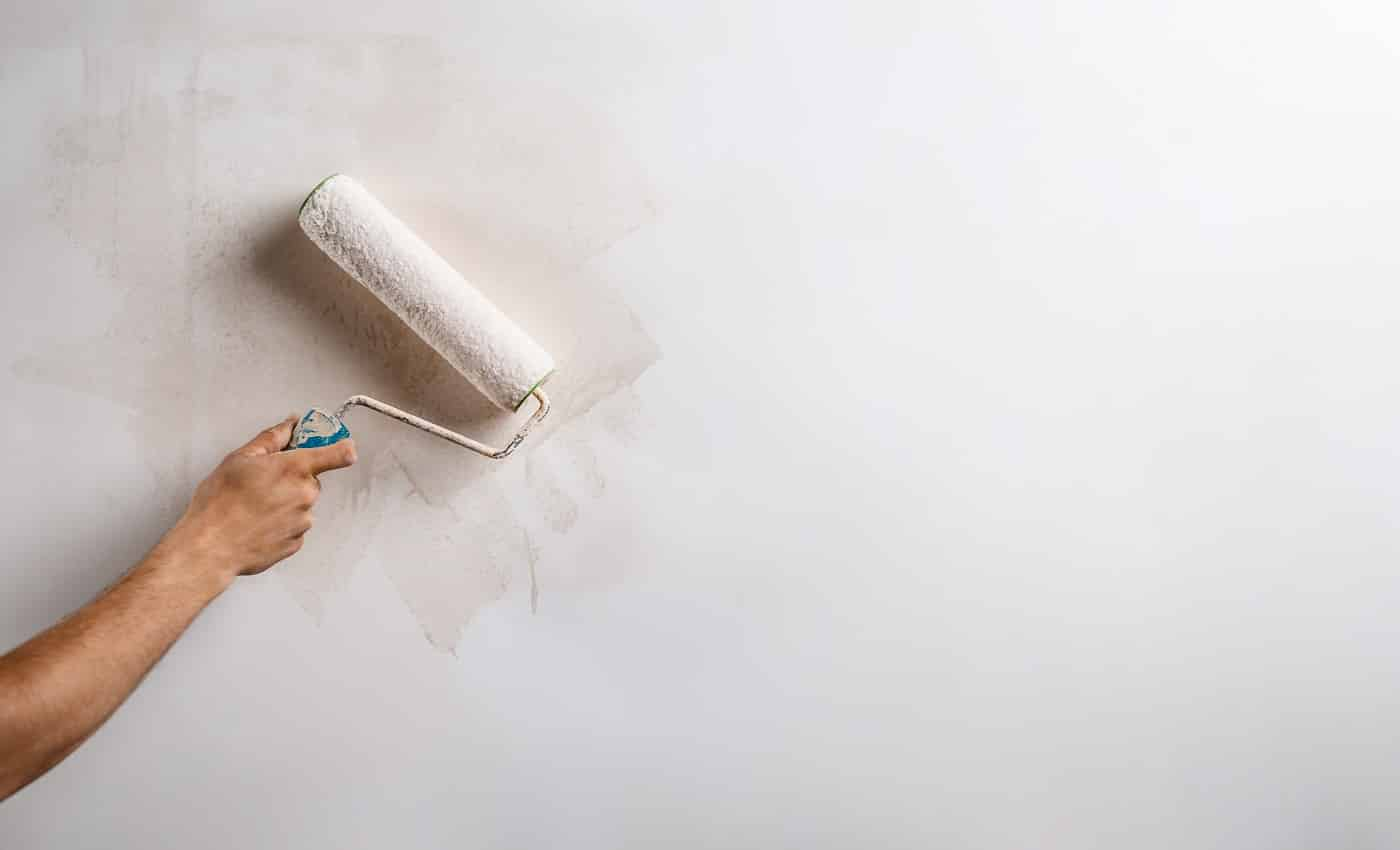 Close up photo of hand painting wall with roller in white color. Copy space.