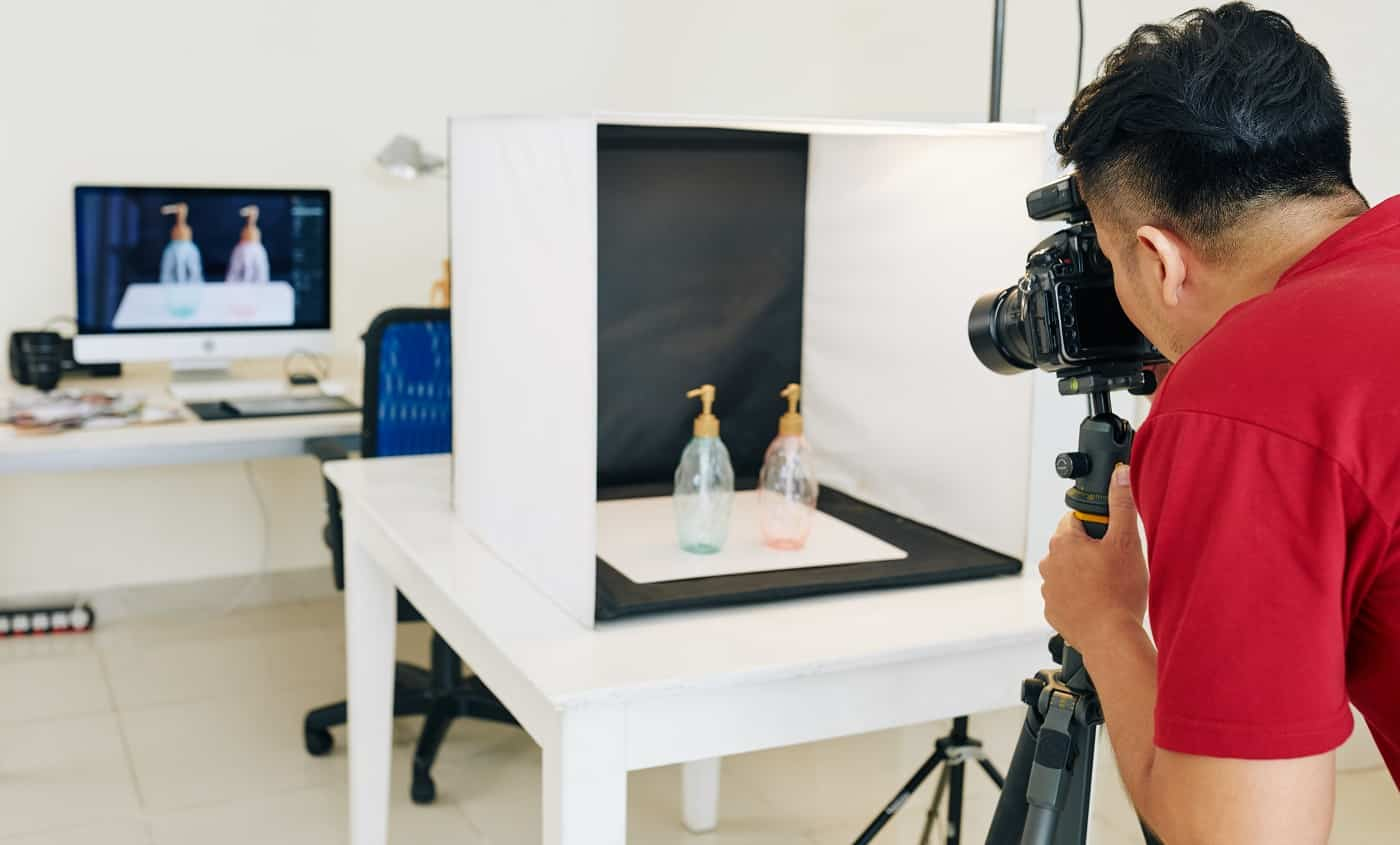 Photographer taking photos of glass bottles in light cube with black background in small studio