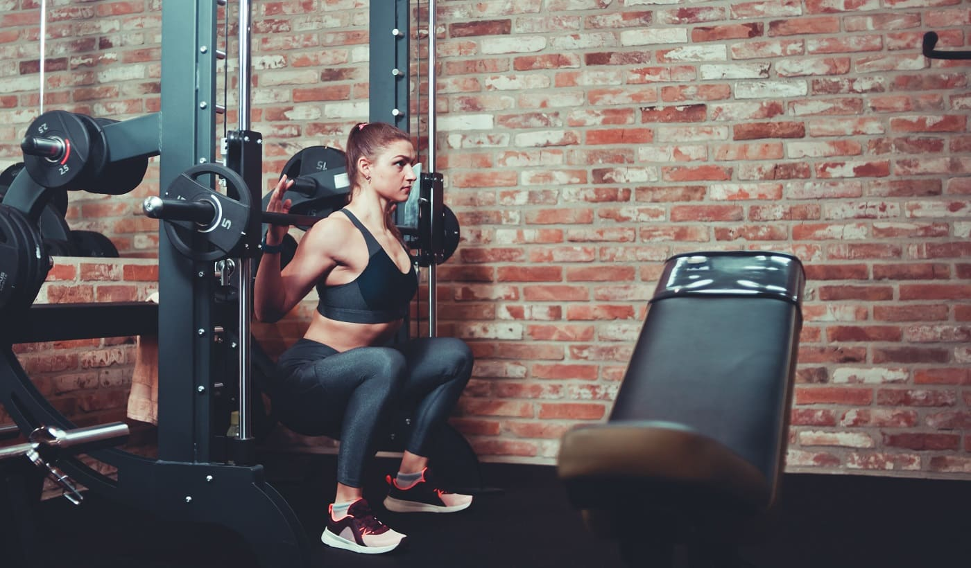 Concentrated sporty girl exercising squatting with barbell at smith machine against brick wall in gym
