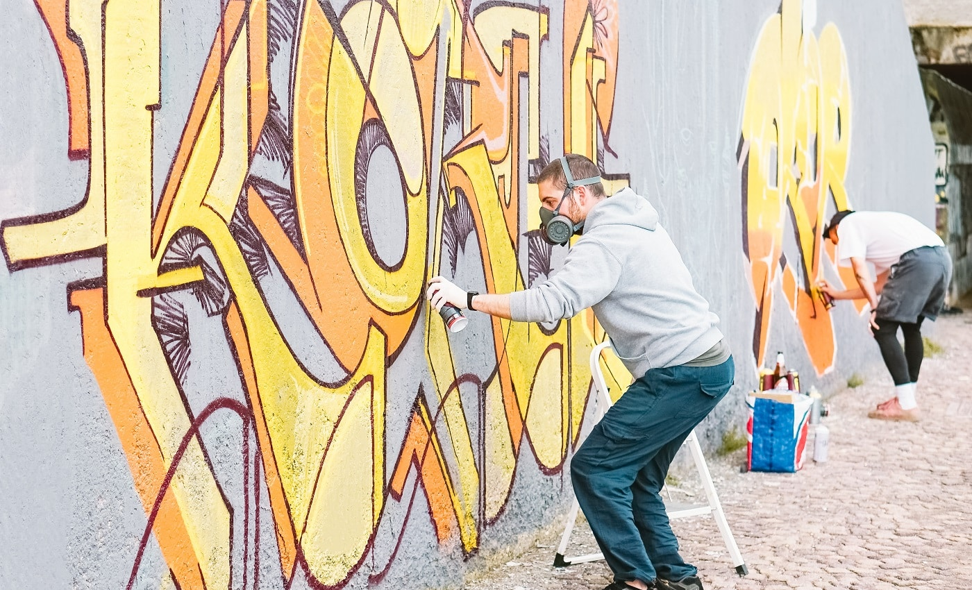 Graffiti artists painting colorful mural on a grey wall - Creative men performing drawing murals - Concept of street and modern art, culture and youth lifestyle