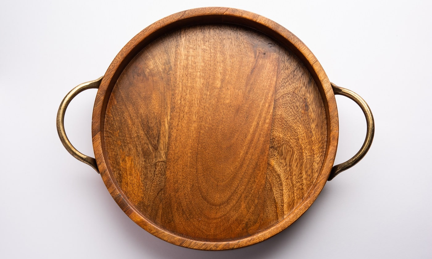 Empty wooden round tray with brass handle on white background
