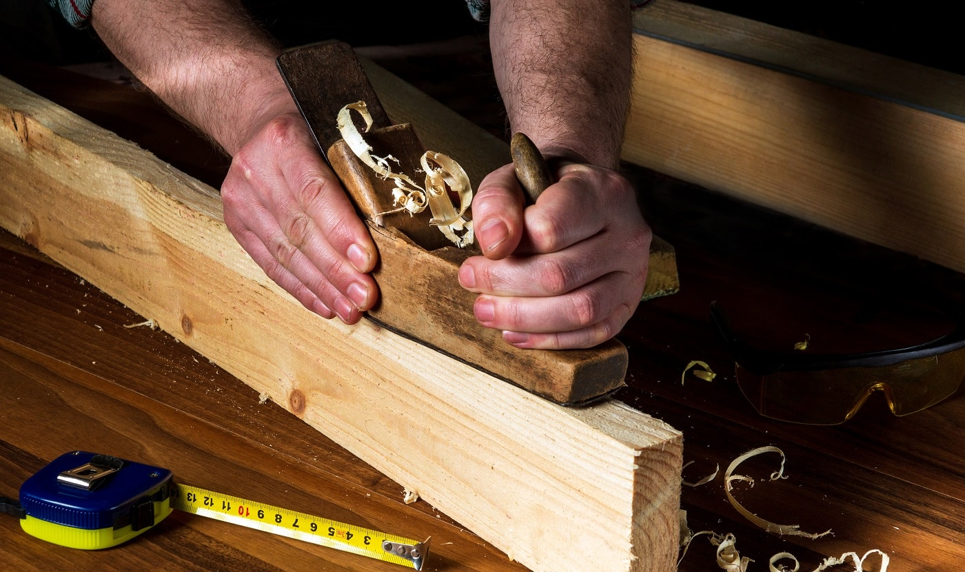 Woodworker using a hand plane to clean up a wooden board. Hands of the master closeup at work. Working environment in a carpentry workshop