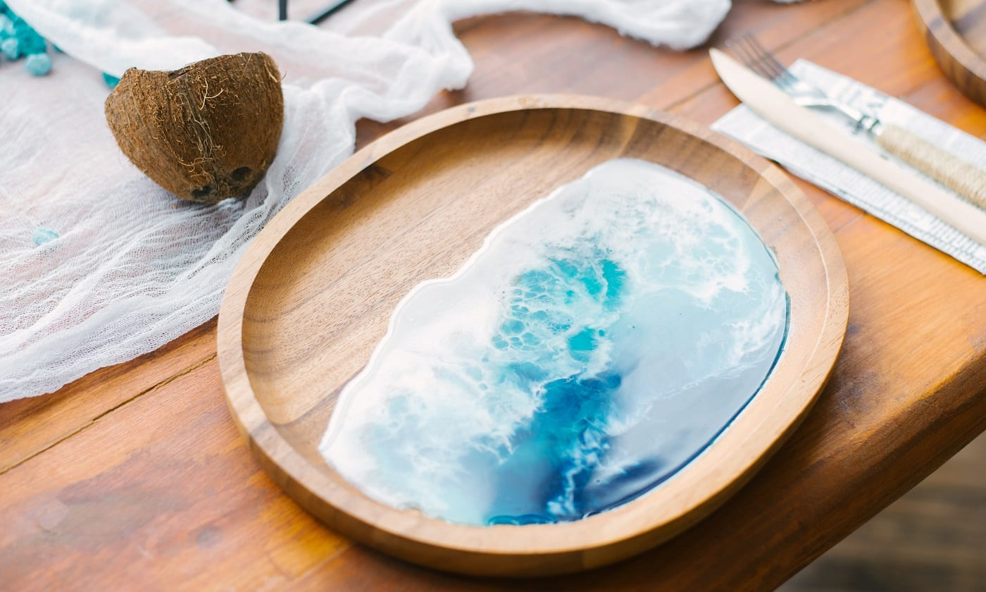 Stylish wooden plate with epoxy resin in the form of the sea or ocean. The trend in the dishes and decor for the home