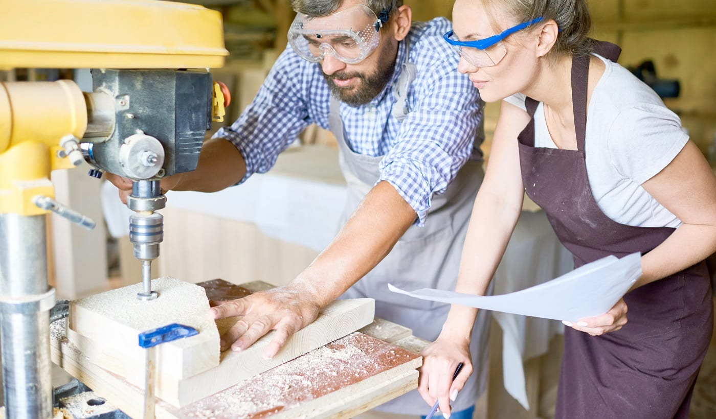 Concentrated bearded carpenter explaining his attractive apprentice how to use drill press machine, interior of spacious workshop on background