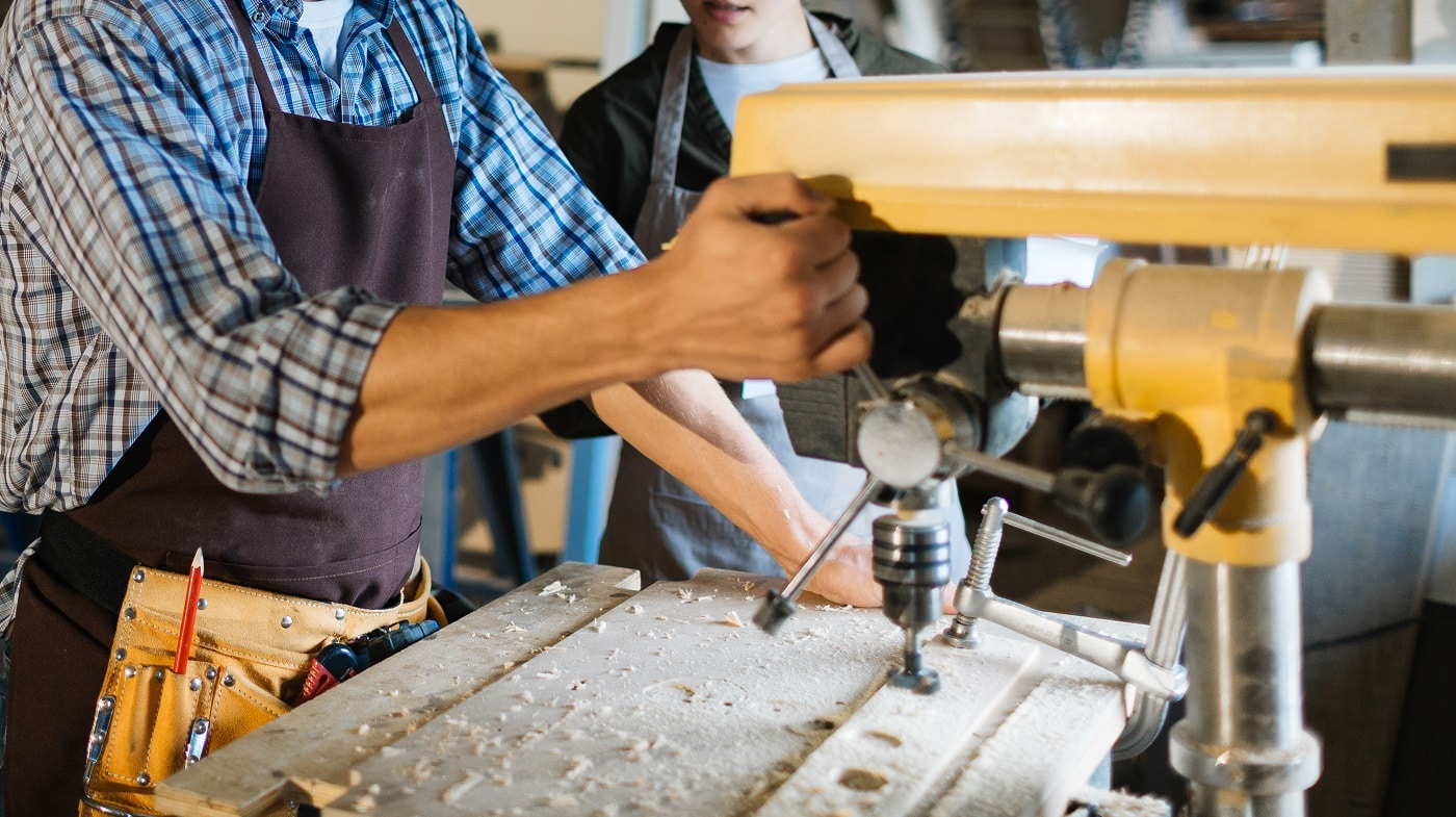 Skillful woodworker in eye and ear protectors explaining his female apprentice how to use drill press, she listening to him with attention