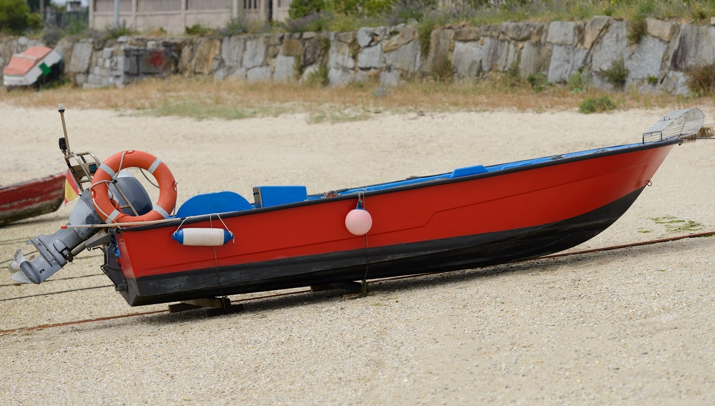 image of red wooden fishing motor boat dries ashore