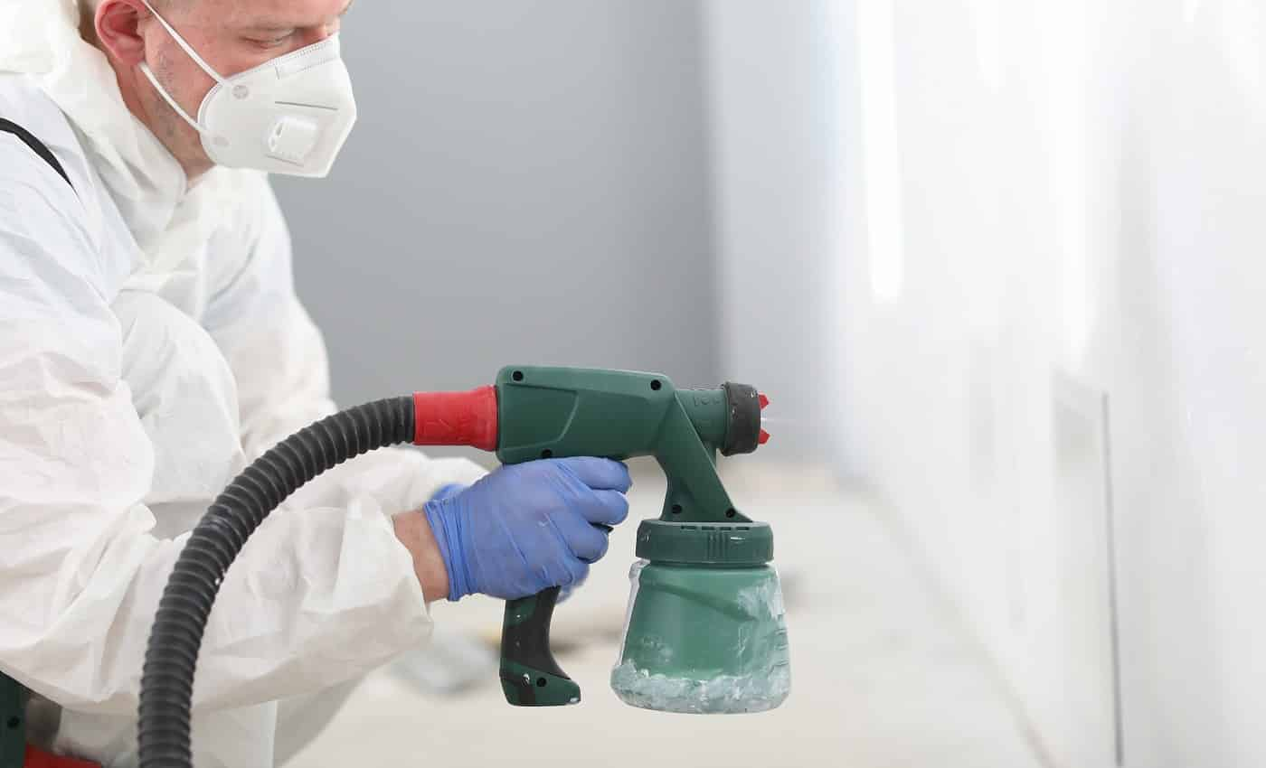 Man in mask holds spray gun in his hands and paints the wall. Courses on mastering new profession concept